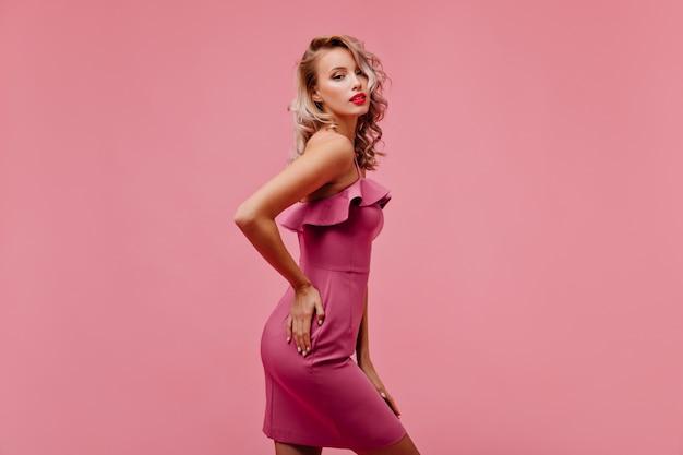 Zmysłowa pewna siebie kobieta stojąca na różowej ścianie