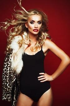 Zmysłowa piękna blondynki kobieta pozuje w czarnej bieliźnie.