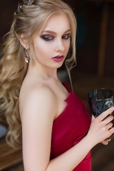 Zmysłowa piękna blondynki kobieta pozuje w czerwieni sukni.