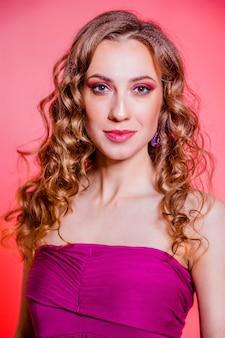 Zmysłowa piękna brunetka dziewczyna z czerwonym makijażem, kręconymi włosami i bordową bluzką, pozowanie na czerwonym tle. zdjęcie pionowe