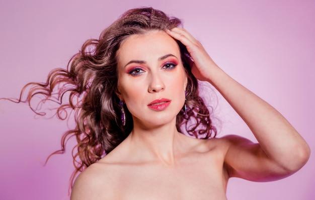 Zmysłowa piękna brunetka dziewczyna z czerwonym makijażem, kręconymi włosami i bordową bluzką, pozowanie na fioletowym tle. poziome zdjęcie
