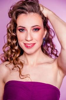 Zmysłowa piękna brunetka dziewczyna z czerwonym makijażem, kręconymi włosami i bordową bluzką, pozowanie na fioletowym tle. zdjęcie pionowe