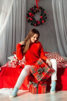 Zmysłowa piękna dziewczyna otwierająca świąteczne prezenty