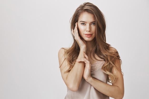 Zmysłowa piękna kobieta dotyka twarzy i uśmiecha się