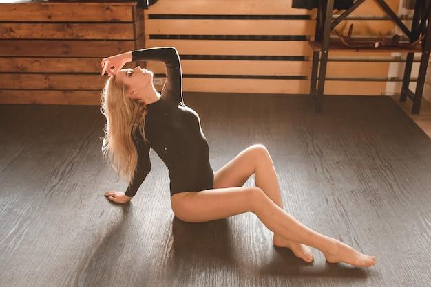 Zmysłowa piękna młoda dama w czarnym body siedzi na podłodze