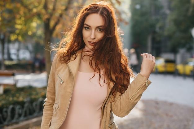 Zmysłowa ruda kobieta w różowej koszuli pozowanie na ścianie natury