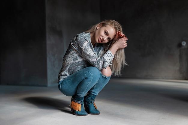 Zmysłowa seksowna młoda blondynka w kowbojskich butach vintage w letniej koszuli w modnych zgranych dżinsach siedzi w pokoju z promieniami słonecznymi