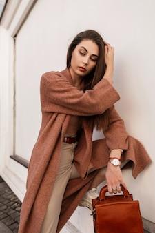 Zmysłowa śliczna młoda kobieta w modnym płaszczu w stylowych beżowych spodniach z brązową skórzaną torebką prostuje długie włosy w pobliżu ściany w mieście. model ładny seksowny elegancki dziewczyna pozuje. wiosenna moda.