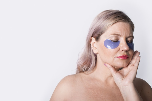 Zmysłowa starsza kobieta z opaskami na oczach pozuje z zamkniętymi oczami i nagimi ramionami na białej ścianie coś reklamującego