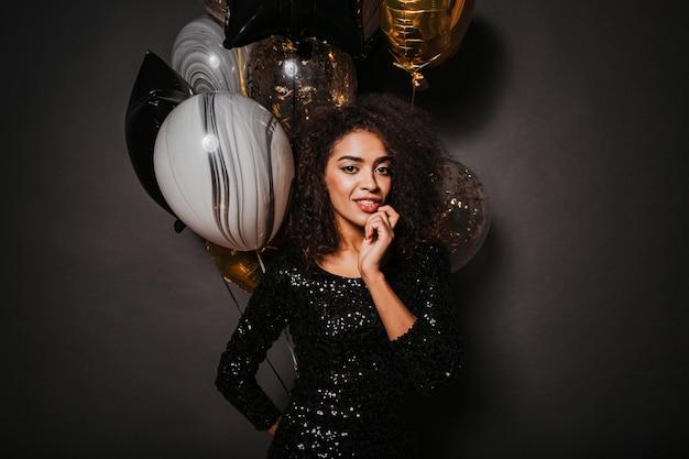 Zmysłowa stylowa kobieta trzyma kilka balonów