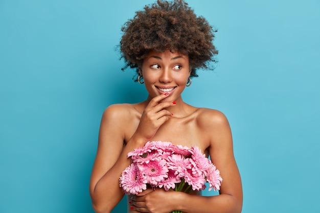 Zmysłowa szczęśliwa modelka o zdrowym nagim ciele, trzyma bukiet różowych kwiatów gerbery, patrzy na bok z rozmarzonym, wesołym wyrazem twarzy, stoi