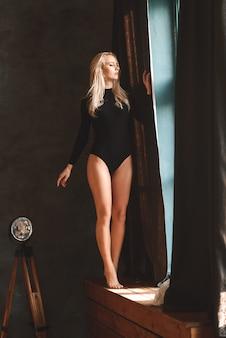 Zmysłowa wspaniała młoda dama w czarnym body pozuje w studio
