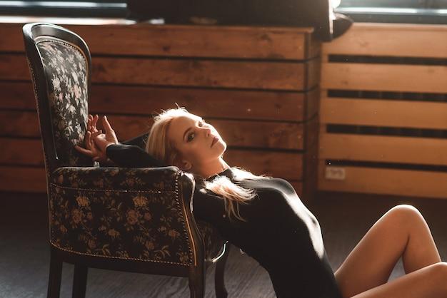 Zmysłowa, wspaniała młoda dama w czarnym body z klasycznym krzesłem