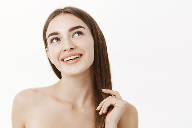 Zmysłowa zalotna i kobieca europejka o pięknej i zdrowej skórze stojąca nago bawiąc się kosmykami włosów