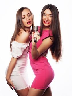 Zmysłowe dziewczyny śpiewają z mikrofonem