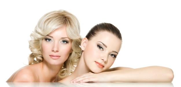 Zmysłowe twarze dwóch pięknych młodych dorosłych kobiet są razem. dziewczyny pozowanie na białym tle
