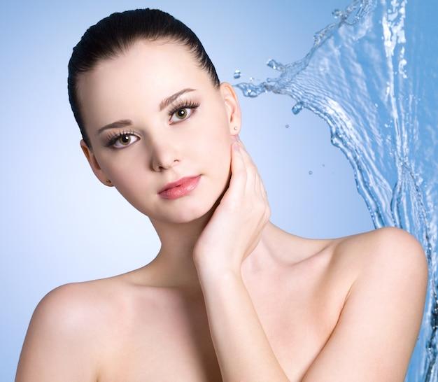 Zmysłowość młoda kobieta ze strumieniem wody - niebieskie tło