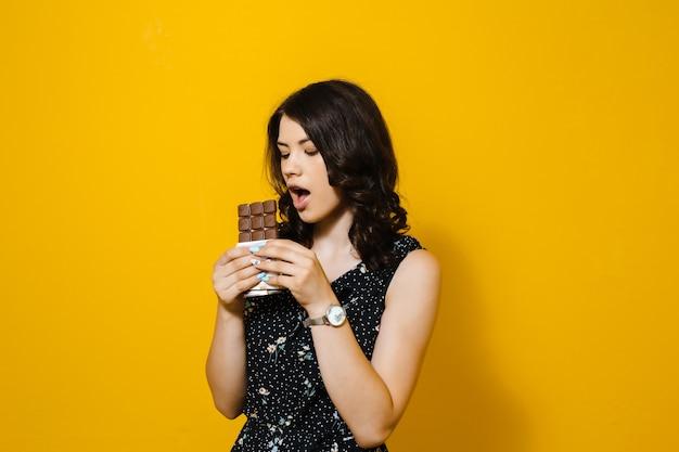 Zmysłowy atrakcyjna młoda kobieta jedzenie i to zdziwiona czekolada na białym tle nad żółtą ścianą