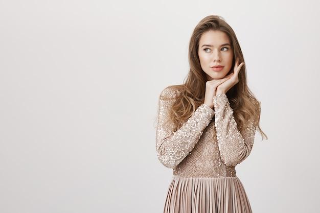 Zmysłowy glamour kobieta w błyszczącej sukience wygląda na lewo
