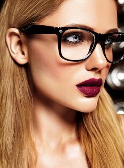 Zmysłowy portret glamour pięknej blond modelki z codziennym makijażem o fioletowym kolorze ust i czystej zdrowej skórze w okularach