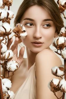 Zmysłowy portret modelki glamour wśród bawełnianych gałązek