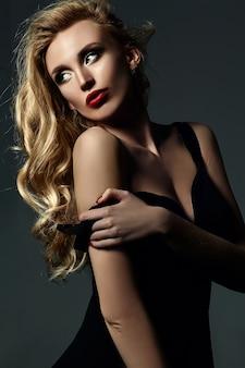 Zmysłowy seksowny portret pięknej blond modelki damy ze świeżym makijażem i zdrowe kręcone włosy
