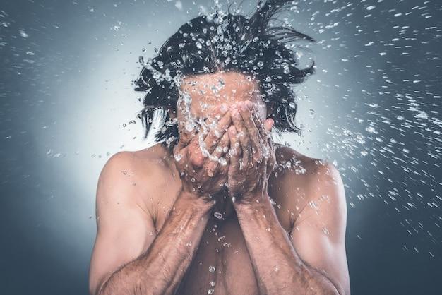 Zmywać. młody mężczyzna bez koszuli myje twarz wodą rozpryskującą się wokół niego
