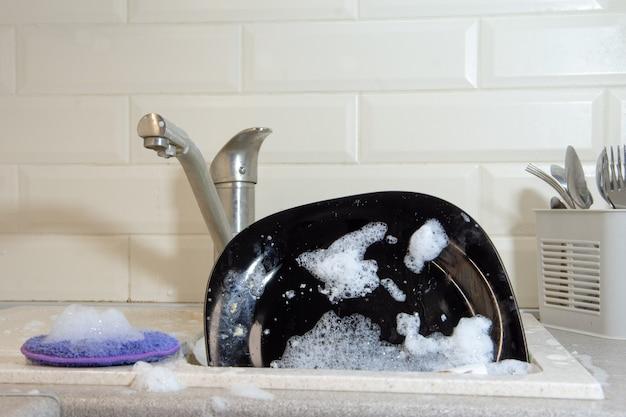 Zmywanie naczyń w kuchni. brudne naczynia, talerze i szklanki, leżą w zlewie w białej pianie. przedni widok. praca domowa