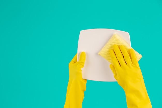 Zmywarka w żółtych rękawiczkach na niebiesko.
