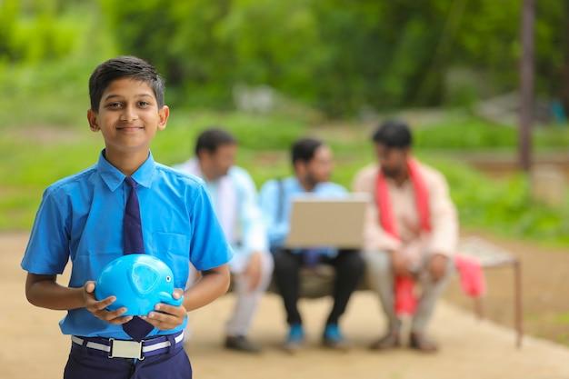 Znaczenie koncepcji oszczędzania: inteligentny indyjski mały chłopiec stojący i trzymający w ręku skarbonkę w domu.