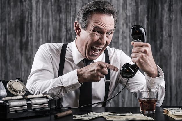 Znajdę cię gdziekolwiek jesteś! wściekły starszy mężczyzna w koszuli i szelkach krzyczy do telefonu, siedząc przy stole z mnóstwem pieniędzy leżących obok niego
