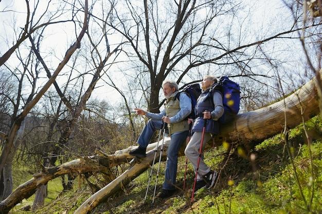 Znajdź najlepszy sposób na życie. starsza rodzina para mężczyzna i kobieta w strój turystyczny spaceru na zielonym trawniku w pobliżu drzew w słoneczny dzień
