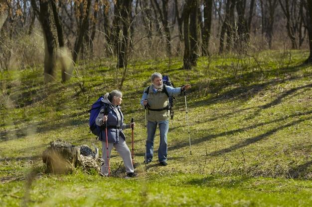 Znajdź właściwą drogę w życiu. starsza rodzina para mężczyzny i kobiety w stroju turystycznym spaceru na zielonym trawniku w słoneczny dzień w pobliżu potoku. pojęcie turystyki, zdrowego stylu życia, relaksu i wspólnoty.