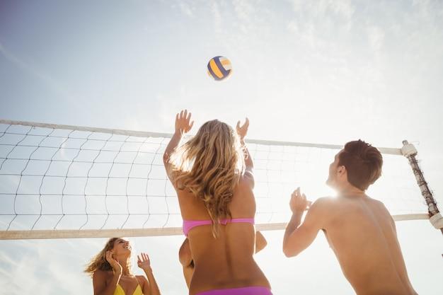 Znajomi grający w siatkówkę plażową