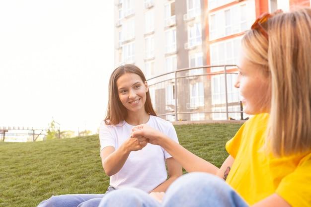 Znajomi komunikujący się ze sobą za pomocą języka migowego