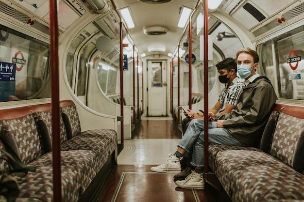 Znajomi korzystający ze smartfona w pociągu w nowej normalności