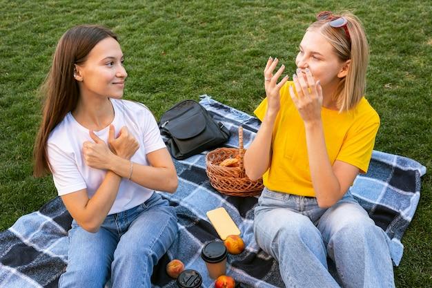 Znajomi na zewnątrz używający języka migowego do komunikowania się ze sobą