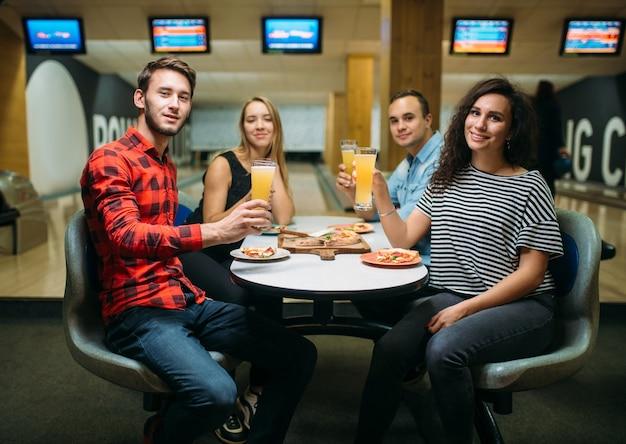 Znajomi piją sok i zjadają pizzę w kręgielni