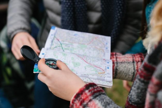 Znajomi podróżni trzymający mapę i kompas