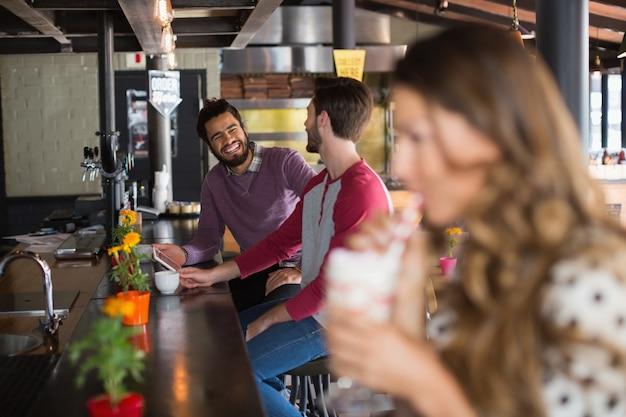 Znajomi rozmawiają siedząc w restauracji