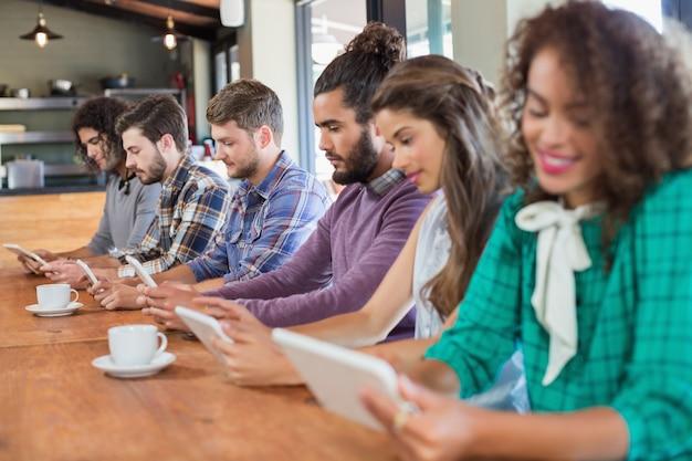 Znajomi używający tabletów cyfrowych w restauracjach