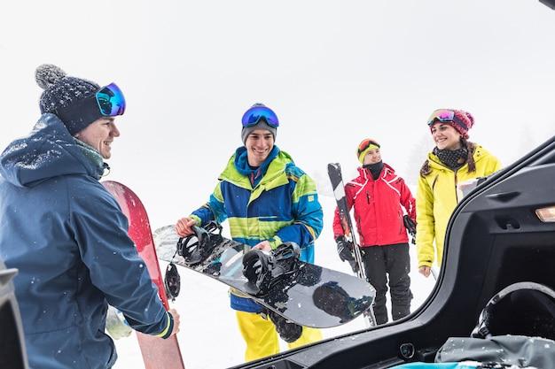 Znajomi z bagażem na narty i śnieg wyładowują rzeczy z samochodu