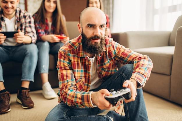 Znajomi z joystickami grają na konsoli telewizyjnej w domu