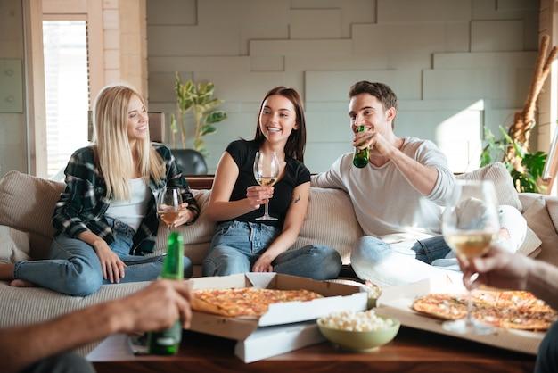 Znajomi z pizzą, winem i piwem rozmawiają i dobrze się bawią
