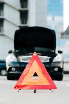 Znak awaryjny z czarnym samochodem w tle
