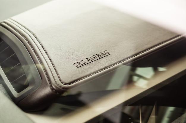 Znak bezpieczeństwa poduszki powietrznej na brązowej skórzanej teksturze w nowoczesnym samochodzie