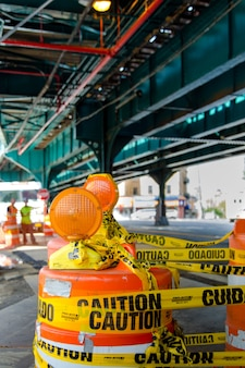 Znak budowy na środku drogi pod mostem metra w nowym jorku