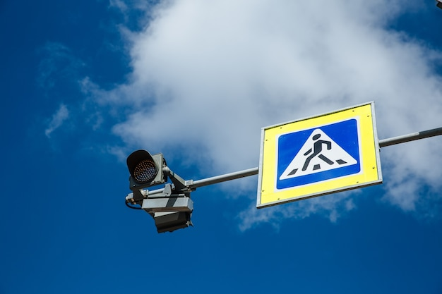 Znak dla pieszych i sygnalizacja świetlna na tle pochmurnego nieba, koncepcja bezpieczeństwa ruchu.