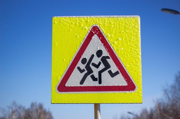 Znak dla pieszych na żółtym tle. w słoneczny zimowy dzień.