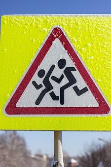 Znak Dla Pieszych Na żółtym Tle. W Słoneczny Zimowy Dzień. Premium Zdjęcia